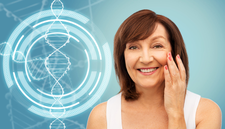 Senior woman touching her face over dna molecule