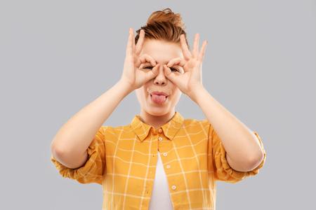 Red haired teenage girl making finger glasses