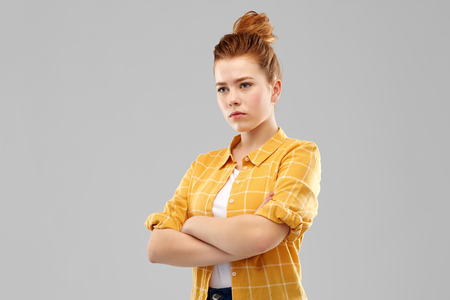 Serious red haired teenage girl with crossed arms