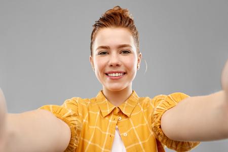 Smiling red haired teenage girl taking selfie