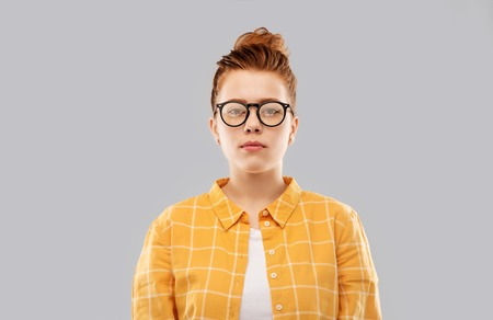 Red haired teenage student girl in glasses
