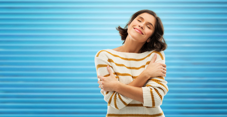 Happy woman in striped pullover hugging herself Stock Photo