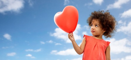 African American girl with heart shaped balloon