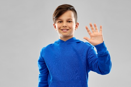 Smiling boy in blue hoodie waving hand