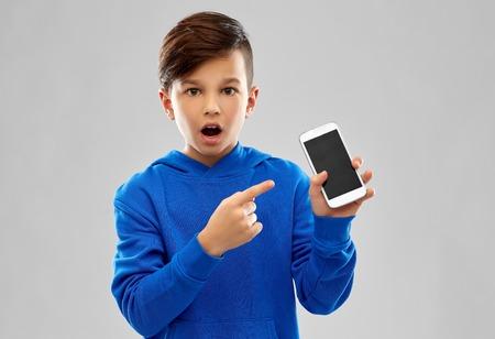 Shocked boy in blue hoodie showing smartphone