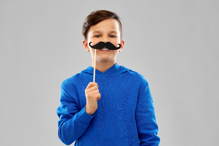 Smiling boy in blue hoodie with black moustaches Banco de Imagens