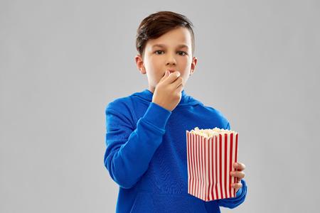 Boy in blue hoodie eating popcorn
