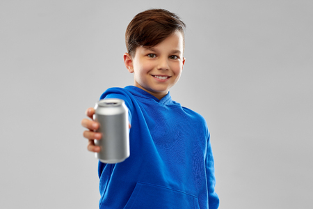 Smiling boy in blue hoodie holding can drink Stockfoto