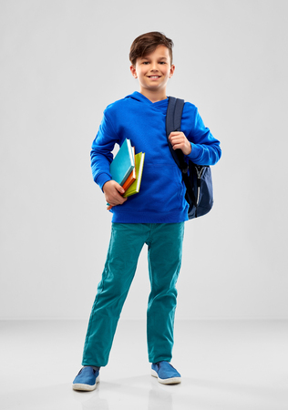 Smiling student boy with books and school bag