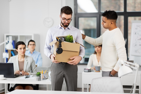 Colleague seeing off sad fired male office worker
