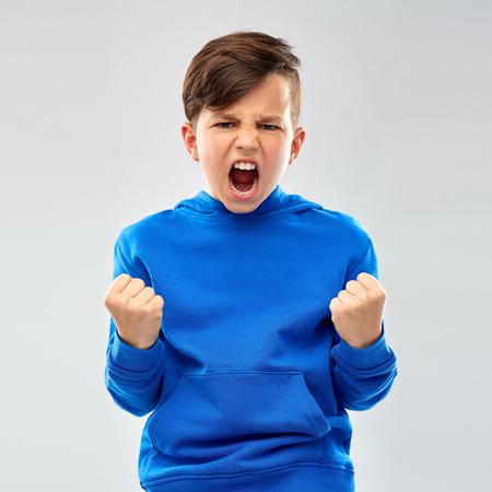 Un niño enojado con sudadera azul celebrando el éxito.