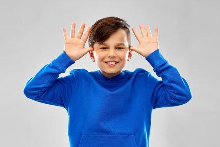 Happy boy having fun and making big ears