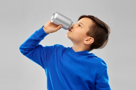 Boy in blue hoodie drinking soda from tin can