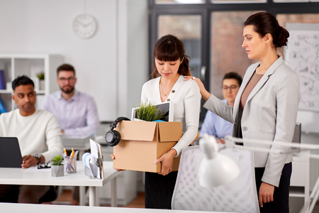 Colleague seeing off fired employee leaving office Stock Photo