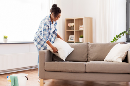 African American woman arranging sofa cushions