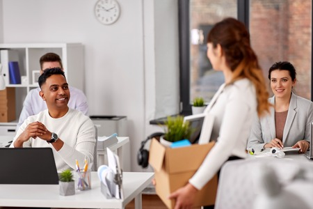 Happy employee with personal stuff at office Imagens
