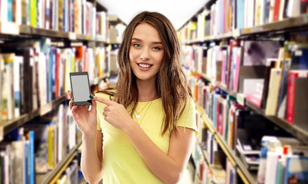 teenage student girl showing smartphone at library