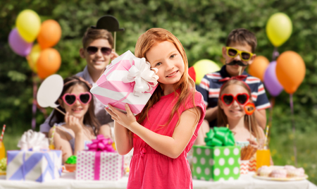 lovely red haired girl with birthday gift at party
