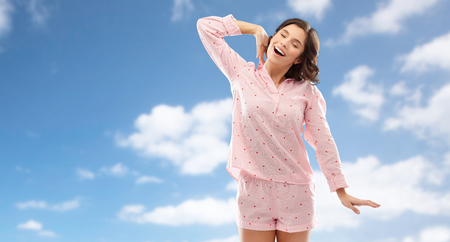 happy young woman in pajama stretching over sky