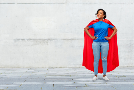 happy african american woman in superhero red cape Stock Photo