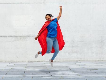 happy african american woman in superhero red cape Reklamní fotografie