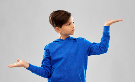boy in blue holding something on empty hands