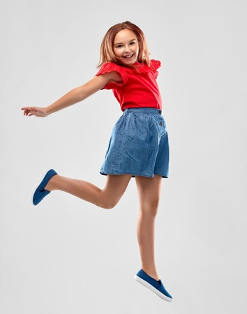 happy smiling girl in red shirt and skirt jumping