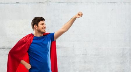 man in red superhero cape over concrete background Stock Photo
