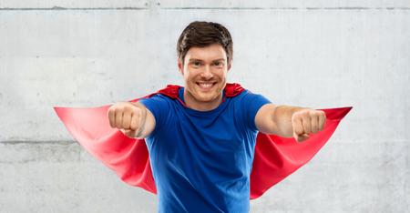 man in red superhero cape over concrete background Reklamní fotografie