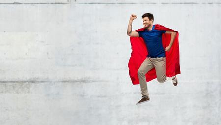 man in red superhero cape jumping over concrete Фото со стока