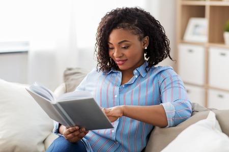 glückliche afroamerikanische Frau, die zu Hause ein Buch liest Standard-Bild