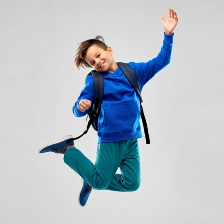 happy smiling student boy with school bag jumping