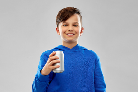 smiling boy in blue hoodie holding can drink