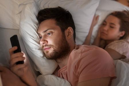 man die smartphone gebruikt terwijl vriendin slaapt Stockfoto