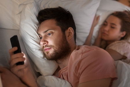 man using smartphone while girlfriend is sleeping 免版税图像