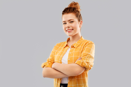 smiling red haired teenage girl with crossed arms
