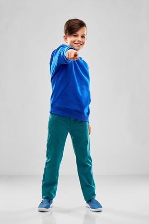 lachende jongen in blauwe hoodie met wijzende vinger