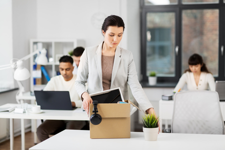 sad female office worker packing personal stuff