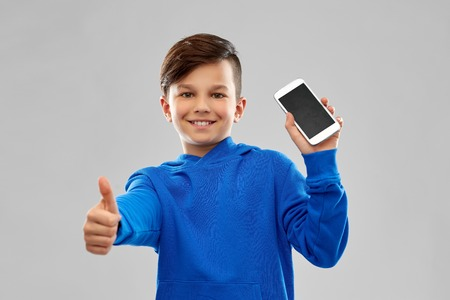 smiling boy showing smartphone and thumbs up