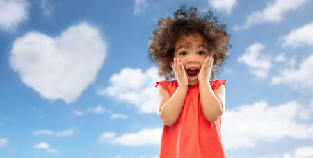 surprised little african american girl over sky Stock Photo