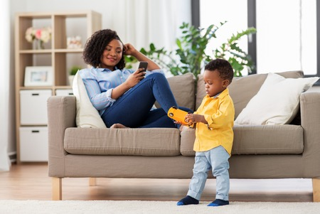baby playing toy car and mother with smartphone