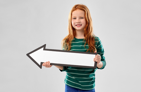 smiling red haired girl with arrow showing to left Фото со стока - 121618295
