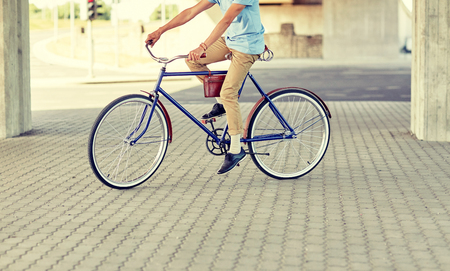 people, style and lifestyle - hipster man riding fixed gear bike on city street