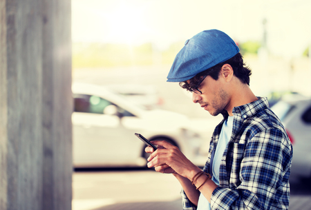 leisure, technology, communication and people concept - hipster man texting message on smartphone on city street Stockfoto