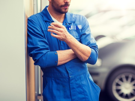service, repair, maintenance and people concept - close up of auto mechanic smoking cigarette 스톡 콘텐츠