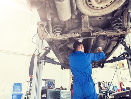 mechanik lub kowal naprawiający samochód w warsztacie