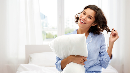 happy woman in pajama with pillow over bedroom