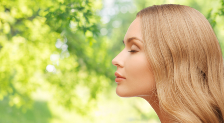 beautiful young woman face over natural background