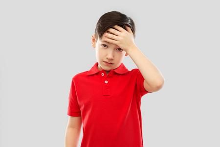 sick boy in red t-shirt suffering from headache