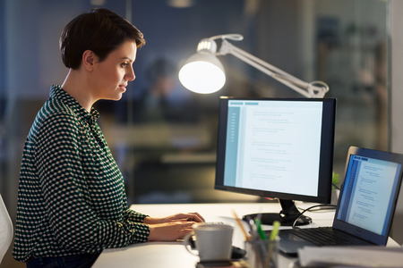 businesswoman working on laptop at night office Stock Photo